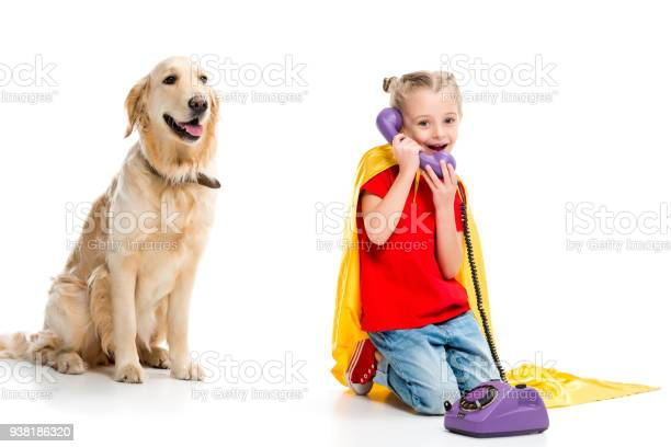Beige dog with smiling little supergirl talking on phone and wearing picture id938186320?b=1&k=6&m=938186320&s=612x612&h=crvdyqis5fwqsyqirndpug7eurl4eeuofog7qpbgmru=