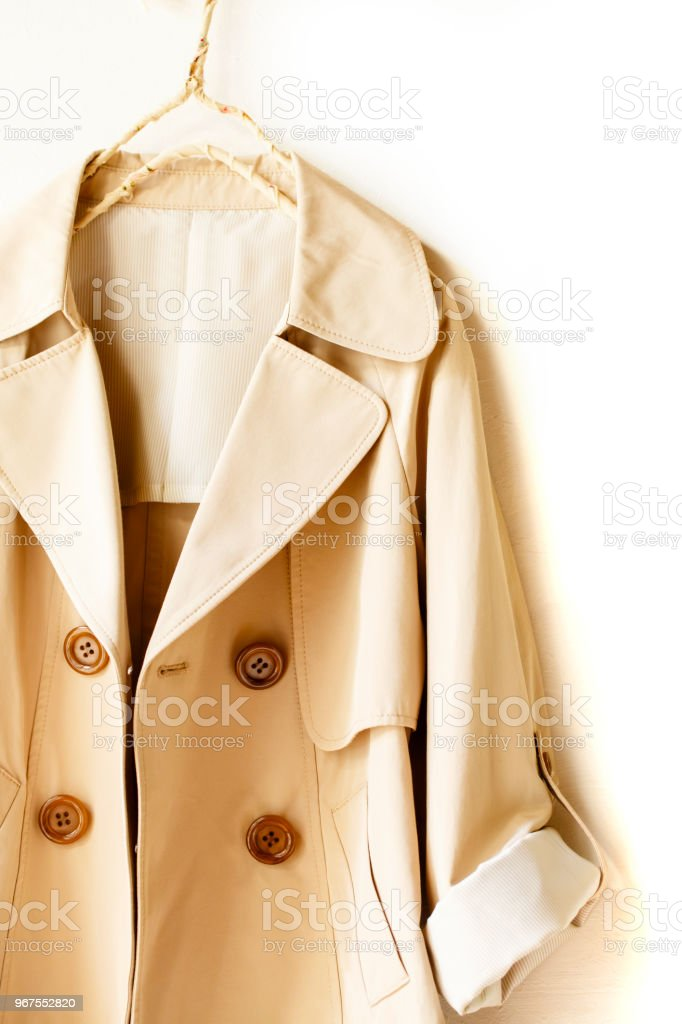A beige elegant trench coat isolated over white. opened in front....