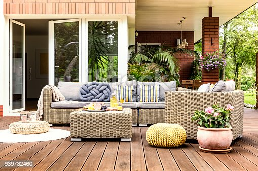 Beige garden furniture with striped pillows on wooden terrace with pink flowers and poufs