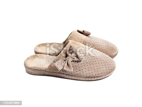 Pair of cozy beige house slippers with bows isolated on white background