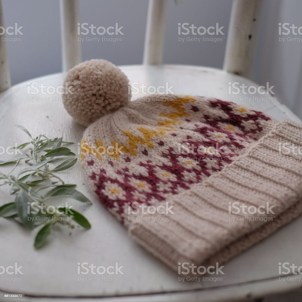 Beige knitted hat with pompon stock photo