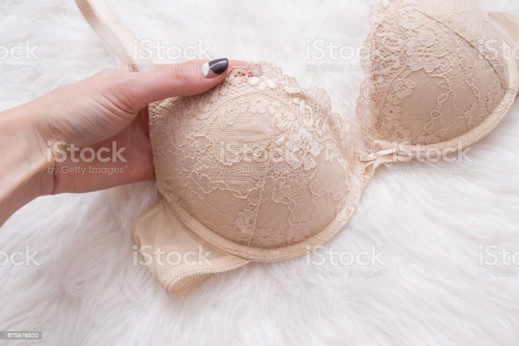 Beige lace bodice in a female hand. White background, top view, close-up stock photo