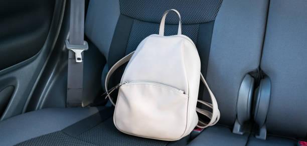 mochila de cuero beige en un gris asiento trasero de un coche. - bolsa objeto fabricado fotografías e imágenes de stock