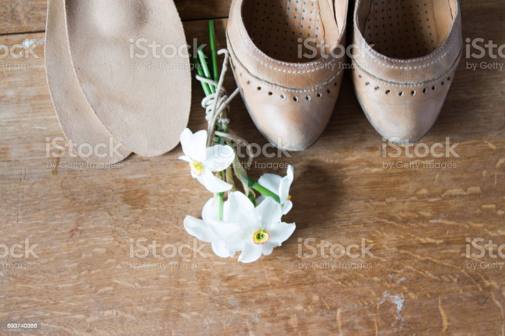 Beige leather shoes with orthopedic insoles and  white daffodils. Wooden background. stock photo