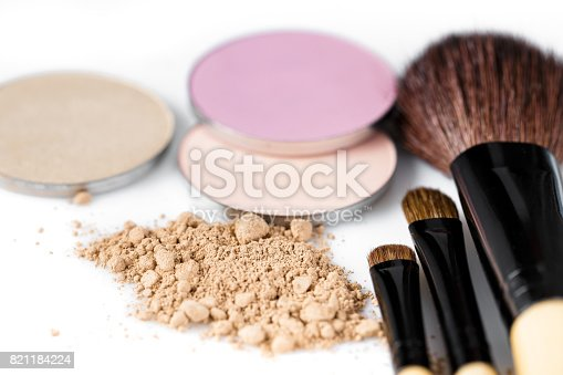 istock beige powder for face, eye shadow and makeup brush  on white background 821184224