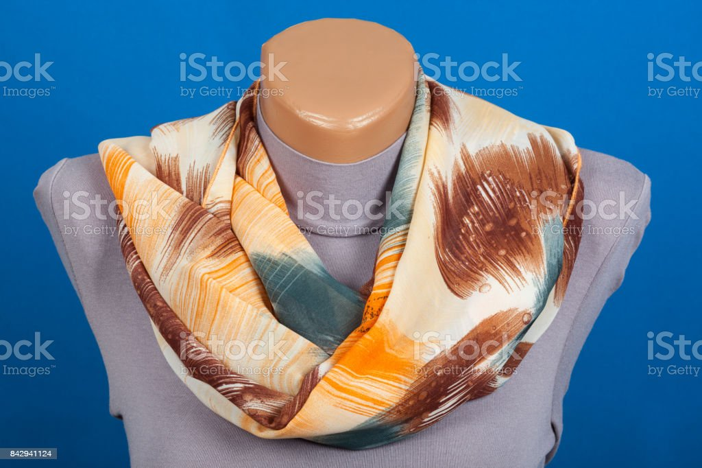 Beige scarf on mannequin isolated on blue background. stock photo