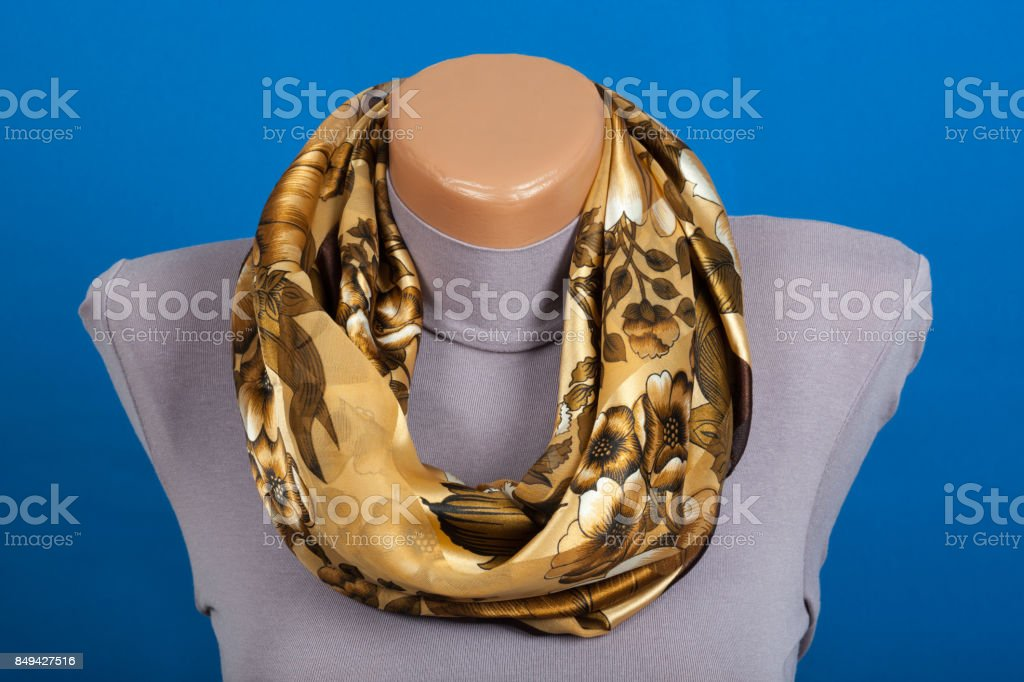 Beige scarf on mannequin isolated on blue background stock photo