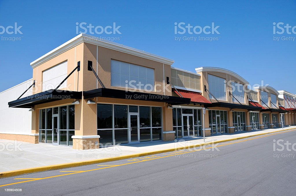 Beige shopping center with available retail space stock photo