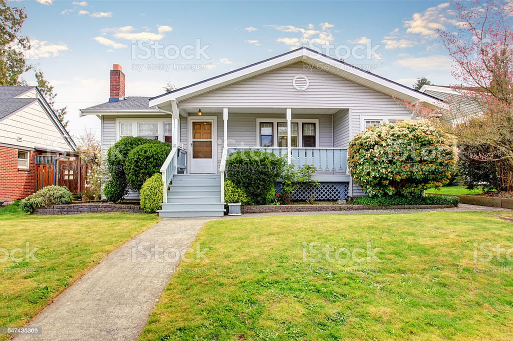 Beige siding house exterior with covered porch. stock photo