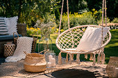A beige string swing with a pillow on a patio. Wicker baskets, a rug and a blanket on a wooden deck in the garden.