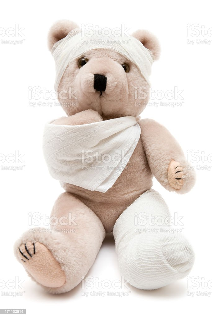 Beige teddy bear wrapped in bandages and a cast stock photo
