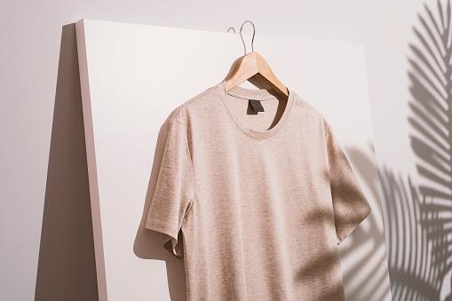 Blank beige t-shirt mockup, template on wooden hanger