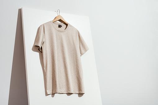 Beige t-shirt mockup, template on wooden hanger