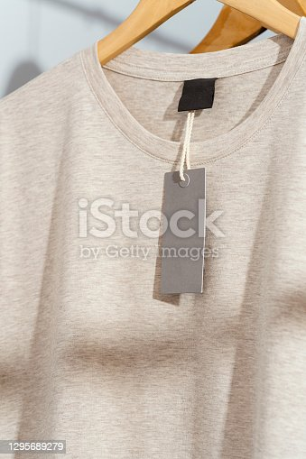 Beige t-shirt with blank price tag on wooden hanger, displayed on clothes rack.