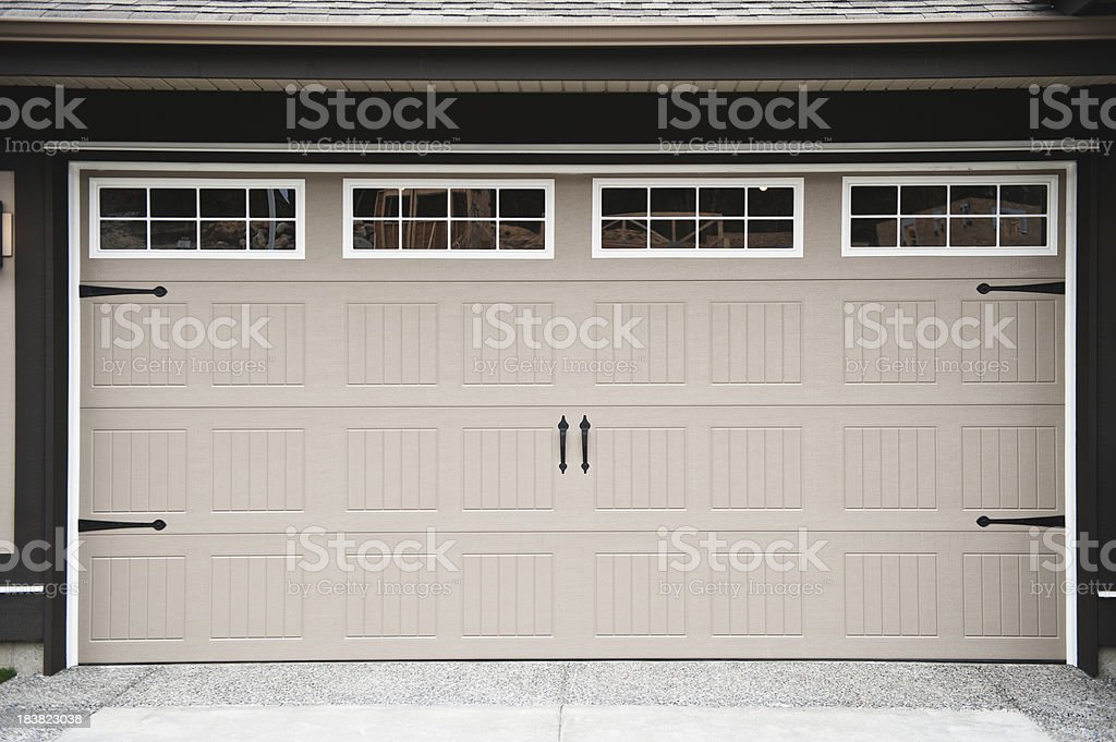 A beige two car garage door with paneled windows along top for Best windows for a garage