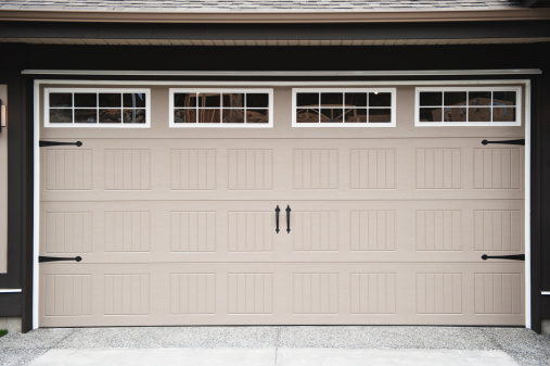 A beige two car garage door with paneled windows along top