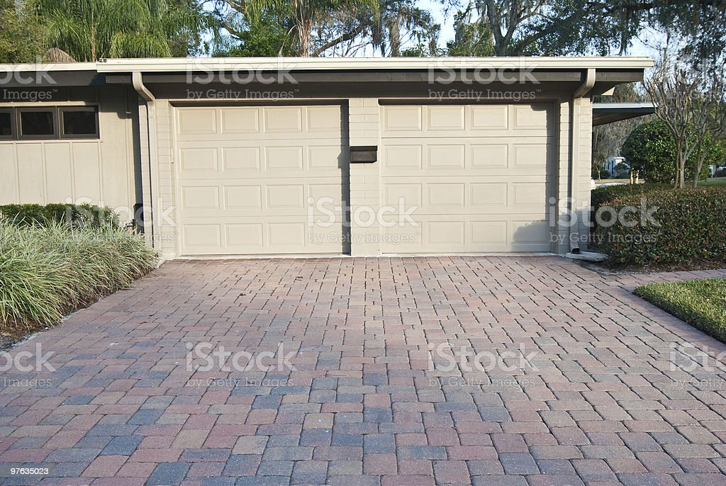Beige Two Car Garage with Brick Driveway attached to Home stock photo