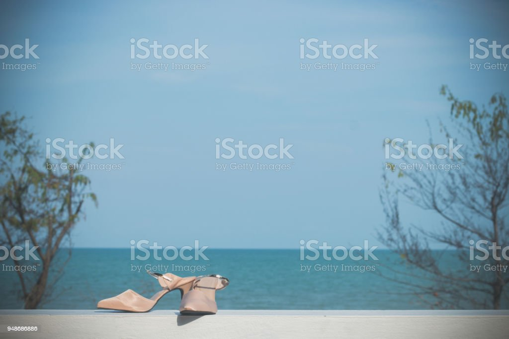 Beige women's high-heeled shoes with seascape view, Fashion female shoes stock photo