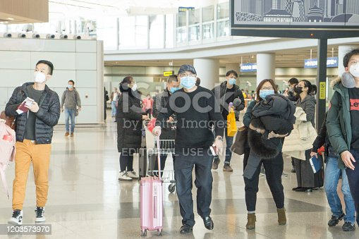 Beijing, China, January 31, 2010:  Beijing Capital International Airport during the outbreak of Corona virus. The virus has rapidly spread and became a global health emergency. Everyone wears mask at the airport.
