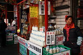 Beijing, China - January 4, 2014 - A Chinese female vendor sells sour milk beverage in the shopping area of Wangfujing.