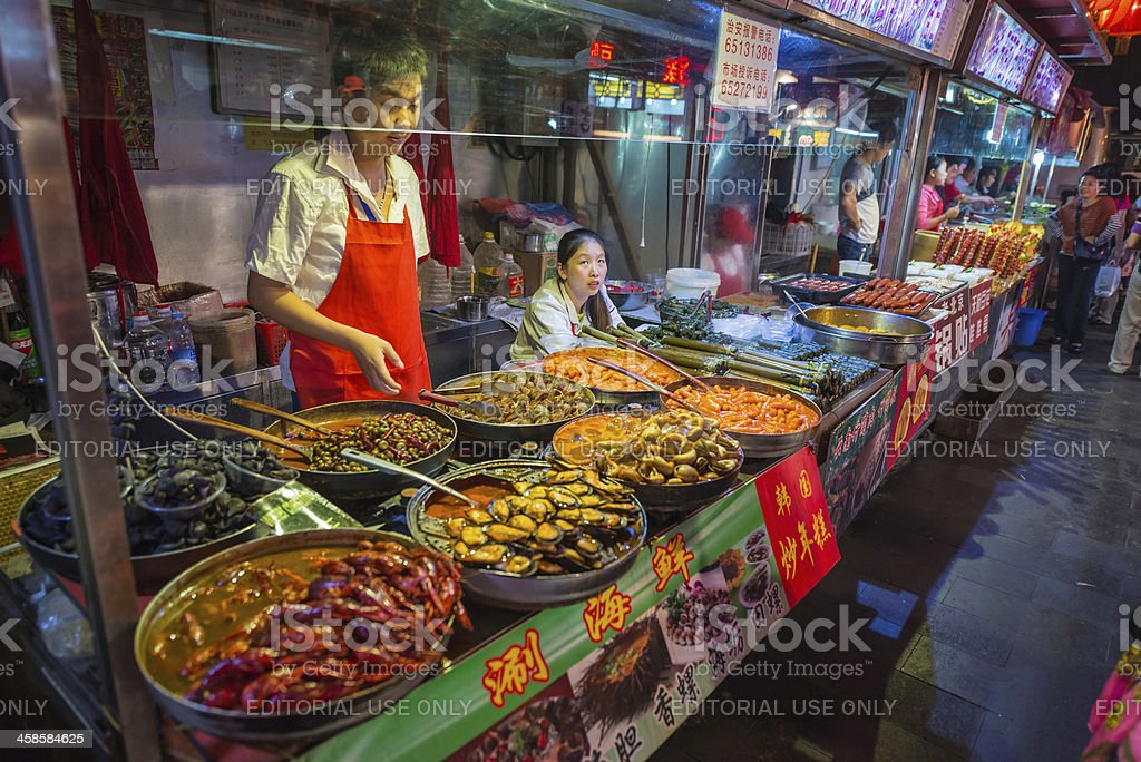 Beijing vendors in colourful night market street food stalls China royalty-free stock photo