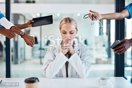 Shot of a doctor looking stressed out working with demanding colleagues in a hospital