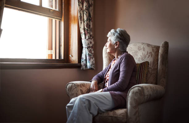 Being alone is something we all have to experience Shot of a senior woman sitting alone in her living room desolation stock pictures, royalty-free photos & images