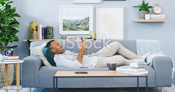 Full length shot of a handsome young man lying down on the sofa in his home and using his cellphone