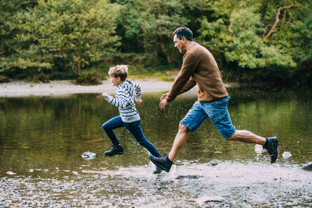 being chased in to the water by dad - close to stock pictures, royalty-free photos & images