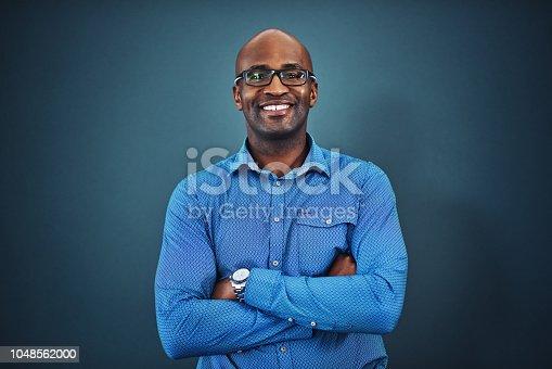 Studio portrait of a confident man posing against a gray background