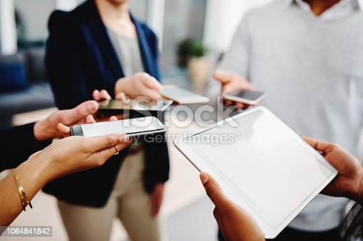 Closeup shot of a group of businesspeople using their digital devices in synchronicity in an office