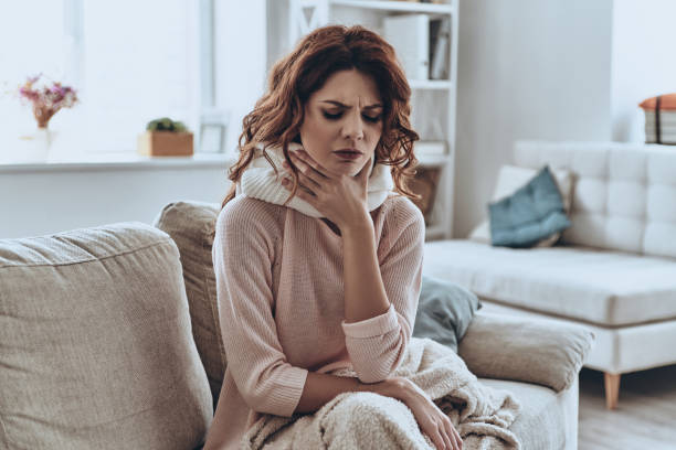 Being ill. Sick young women covered with blanket coughing while sitting on the sofa at home throat stock pictures, royalty-free photos & images