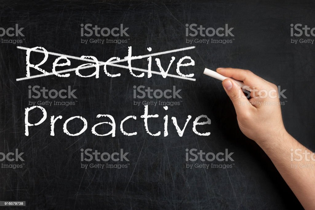 Being Proactive not Reactive crossed blackboard chalkboard stock photo