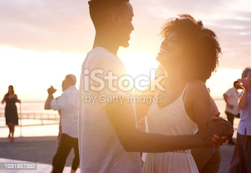 Cropped shot of a young attractive couple dancing on the promenade at the beach