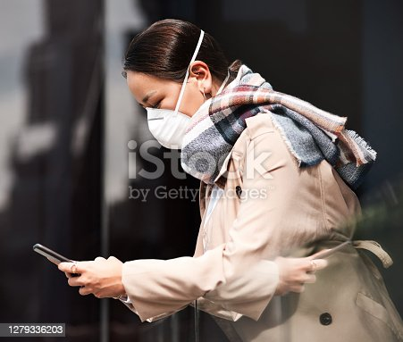 Shot of a young woman wearing a mask and using a smartphone on the balcony at home
