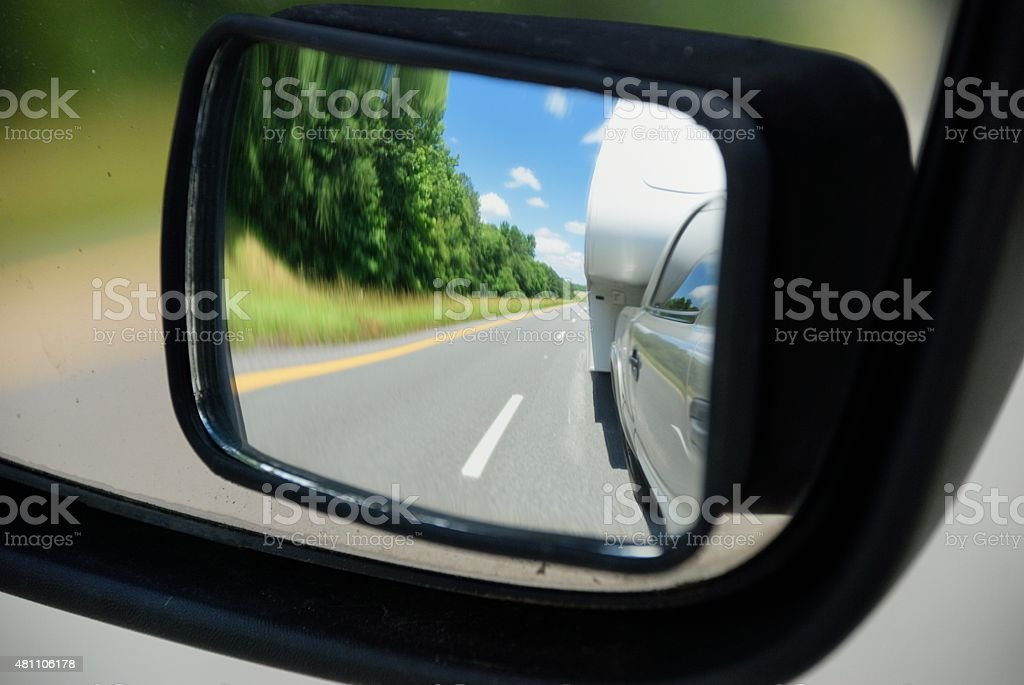 RV being towed in rear view mirror stock photo
