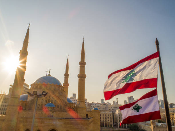 beirut, lebanon 2019 : drone shot of martyr square, showing the lebanese flag in foreground  along with mohammad al amine mosque and st. george church in the background, during the lebanese revolution - beirut стоковые фото и изображения