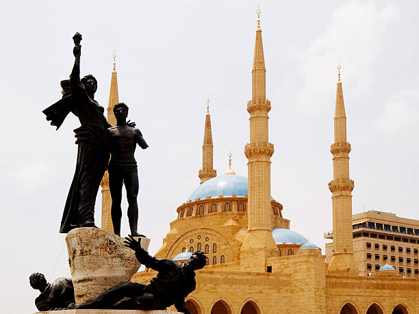 Beirut - Martyr Square The statue on the Martyr Square in Beirut is full of bullet holes from the civil war. In the background is the Al-Amine Mosque. beirut stock pictures, royalty-free photos & images