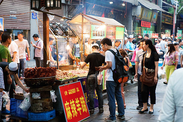 Beiyuanmen Moslem Street in Muslim Quarter - Xi'an, China Xi'an, China - May 24, 2014. People buying food from street vendor on Beiyuanmen Moslem Street in Muslim Quarter of Xi'an, China. The street is filled with many tiny shops and vendors. muslim quarter stock pictures, royalty-free photos & images