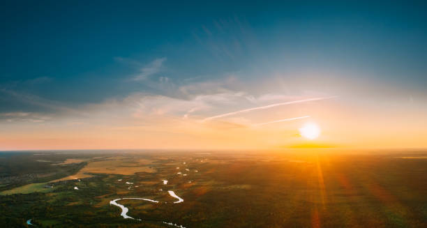 Belarus. Aerial View. Beautiful Sunset Sun Sunshine Above Summer Green Forest And River Landscape In Sunny Evening. Top View Of European Nature From High Attitude In Summer Sunrise. Bird's Eye View stock photo