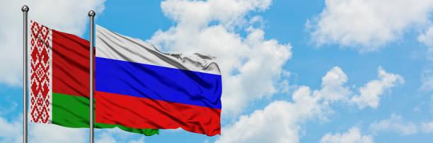 flaga białorusi i rosji macha na wietrze przed białym pochmurnym błękitnym niebem razem. koncepcja dyplomacji, stosunki międzynarodowe. - białoruś zdjęcia i obrazy z banku zdjęć