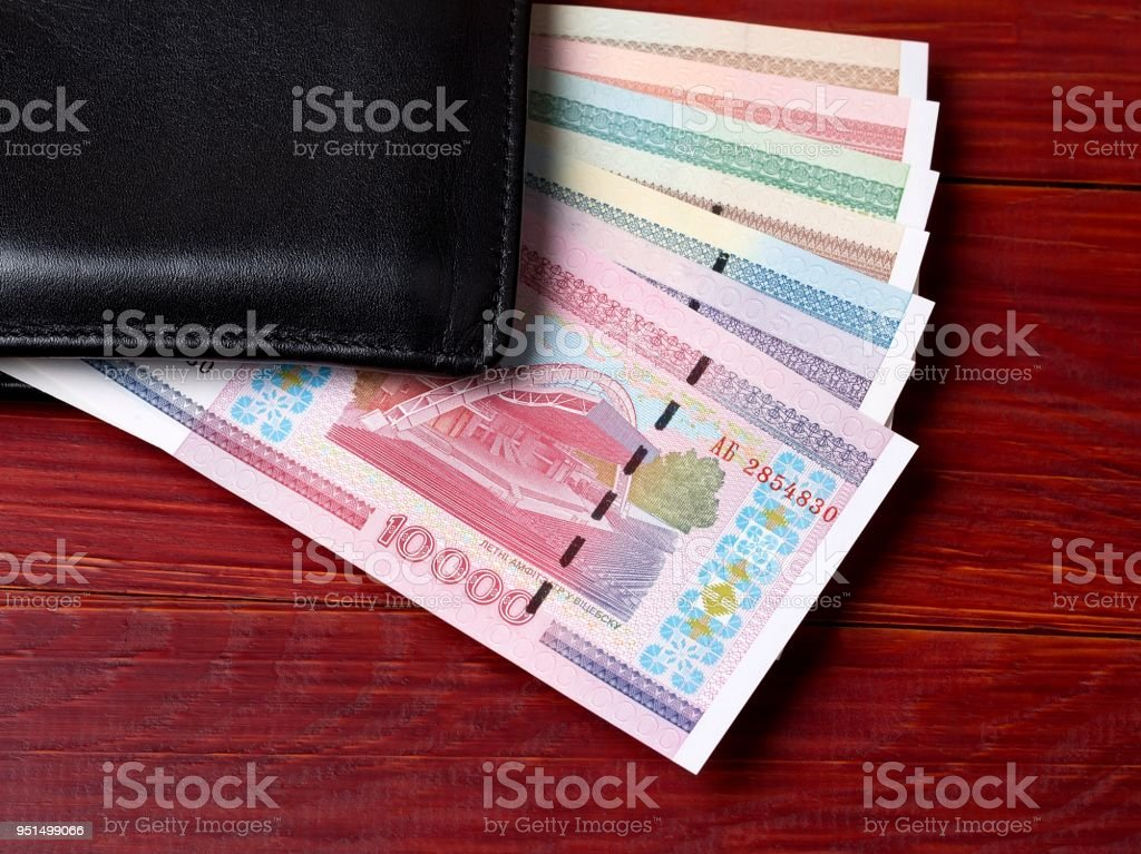 Belarusian ruble in the black wallet on a wooden background