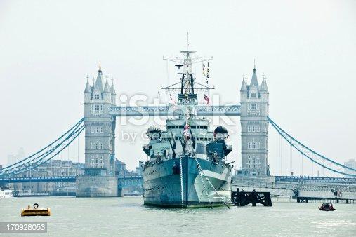 HMS Belfast battle ship on Thames river against Tower Bridge. Blue toned.