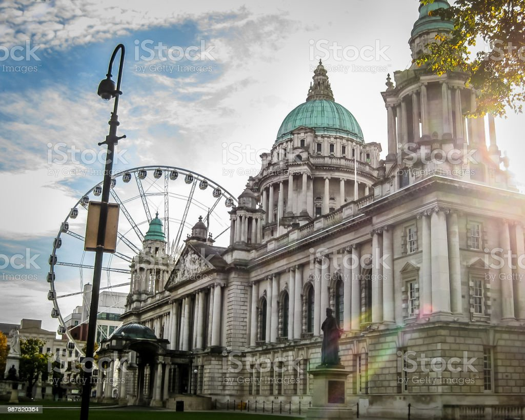 Pasillo de ciudad de Belfast en Irlanda del norte con la llamarada del sol y la rueda de la fortuna en el fondo - foto de stock