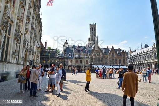 Bruges, Belgium - June 22, 2019: Tourist walking in front of the Provinciaal Hof (Province Court), on the market place of Bruges.