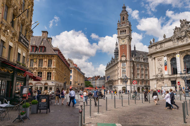 Belfry of the Chambre de Commerce and Opera House in Lille, FR. Lille, France - 15 June 2018: People walking in the Theatre Square. Belfry of the Chambre de Commerce and Opera House in the background. hauts de france stock pictures, royalty-free photos & images