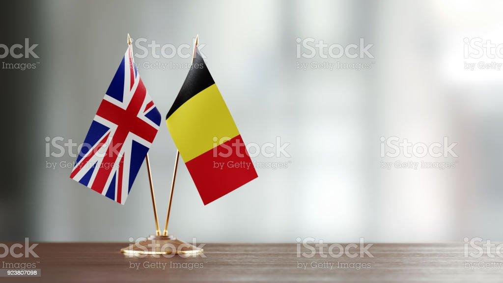 Par de bandeira britânica e belga em uma mesa sobre fundo desfocado - foto de acervo