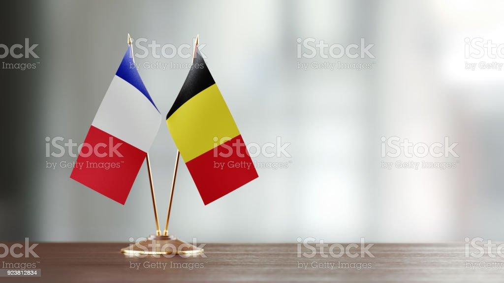 Par de bandera belga y francés en un escritorio sobre fondo Defocused - foto de stock