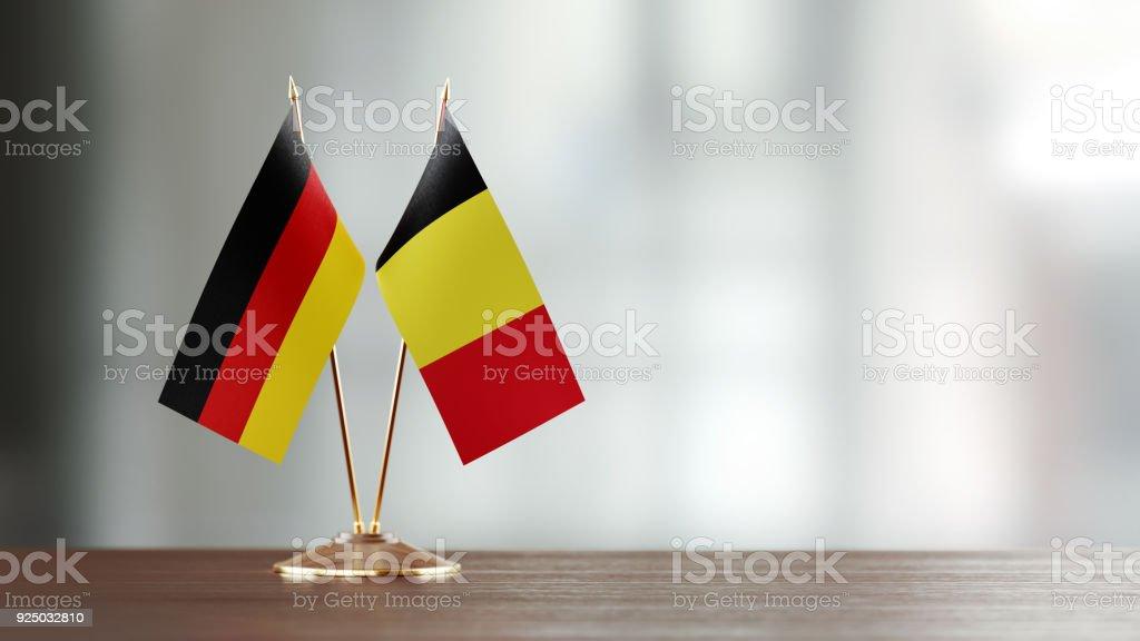 Paire de drapeau belge et allemand sur un bureau sur fond défocalisé - Photo