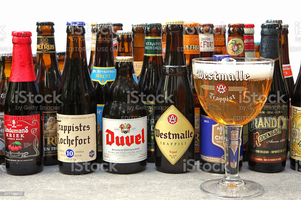 Belgian Beer Bootles and a Glass of Westmalle Trappist Tripel stock photo